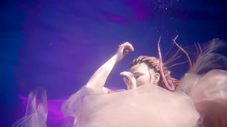 mysticism : young woman with dreadlocks on her head floating under the sea in the sea Stock Footage