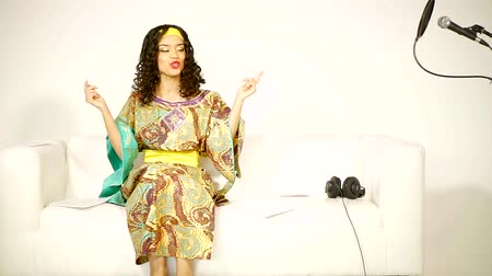 aluna : African American girl in national dress sitting in a white Studio on the couch and trying to compose a new song