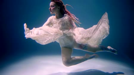 лазурный : Stunning young model is floating in pose underwater.