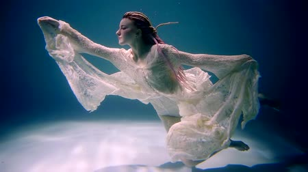 costumes : tranquil graceful woman is floating slowly near bottom of sea and sun is shining on her figure