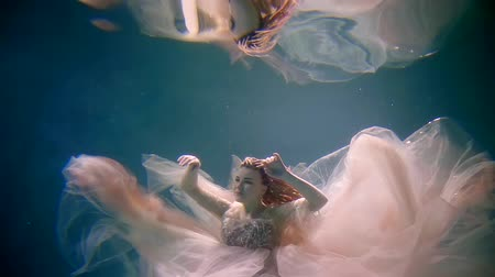 mermaid : beautiful romantic bride is swimming underwater in pool and her reflection in surface is above her