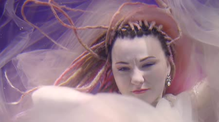 afloat : face of woman with dreads, she is floating underwater between white fabric , moving it out and looking in camera