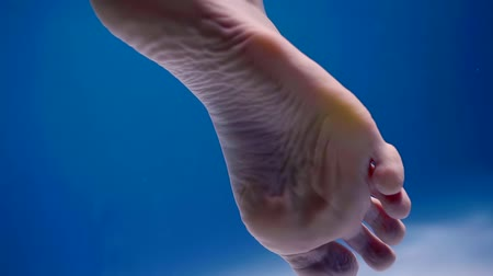 afloat : one bare female foot in water in blue background, underwater shot of body part