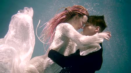 mermaid : bride and groom are hugging to each other and diving inside clear water of sea, they are wearing wedding suits