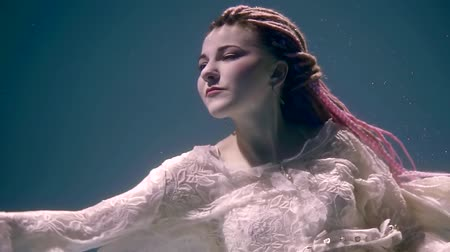 mermaid : glamorous young woman is wearing white lace dress is dancing underwater, moving hands, with open eyes