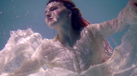 afloat : dramatic shot of sinking romantic girl inside water of lake, face with ripple of sun rays on skin