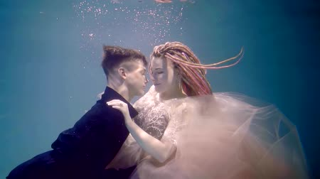 afloat : young loving couple is embracing tenderly underwater in pool, girl and boy are moving up and touching surface