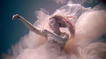 afloat : mermaid is in underwater space, stretching her hands to side and looking, keeping afloat