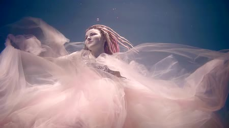mermaid : romantic dreaming girl is floating underwater in sea and touching by hands her beautiful pink dress Stock Footage