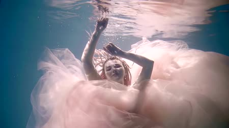 mermaid : fairytale sea nymph is diving inside clear water, her pink chiffon dress is floating around