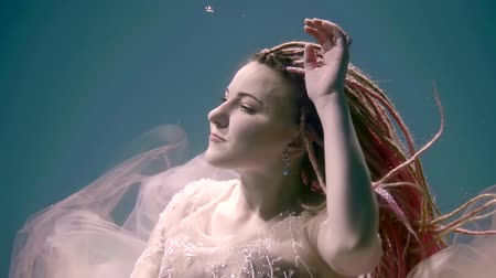 mermaid : face of pretty woman with dreadlocks, swimming underwater, wearing white dress, looking up