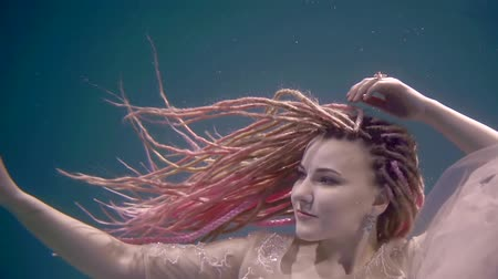 afloat : mermaid with pink dreadlocks is floating underwater, looking around and moving hands