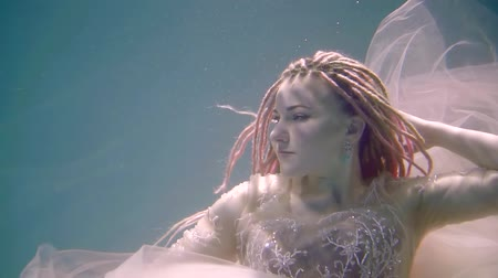 afloat : graceful woman is keeping afloat with open eyes inside water of lake, underwater close-up Stock Footage