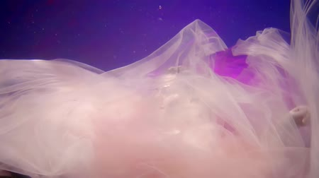 afloat : young blonde woman is sinking in water of pool and pink and purple silk fabric is floating around Stock Footage