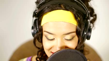 vokální : african woman is singing in a large professional microphone in a record studio, close-up