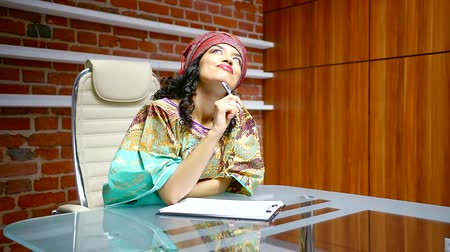 külföldi : dark haired woman is wearing traditional turban on head is sitting in office and filling papers