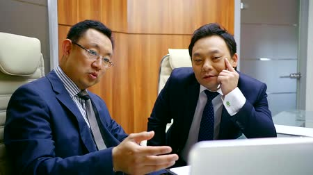 zasedací místnost : two asian men wearing suits with ties are looking on a display of notebook and discussing, sitting in a meeting room Dostupné videozáznamy