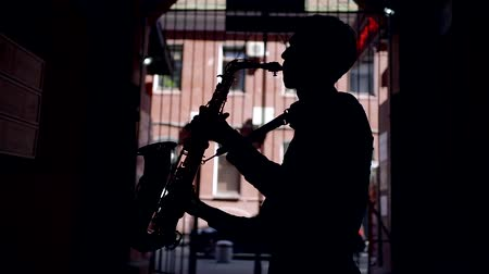 обед : silhouette of a young musician saxophonist. play a wind musical instrument on the street in the tunnel of the building