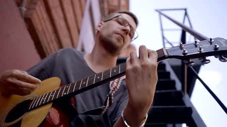 resfriar : young musician with glasses plays the melody guitar on the streets. plan bottom focus on a musical instrument