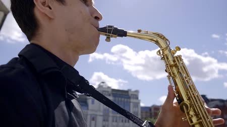szakszofon : young musician saxophonist plays jazz on his instrument in a Sunny summer day on a city street