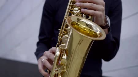 jazzman : close-up. young male musician playing saxophone on the street in the afternoon. to blow a jazzy tune Stock Footage