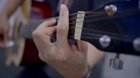 strum : close-up. the hand of the musician on the guitar fretboard clamps the strings. on the background of the hand is played the music