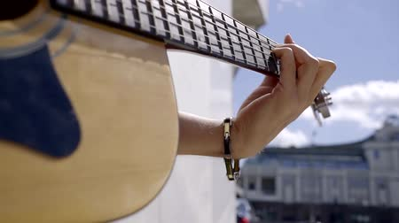 гитара : close-up. acoustic guitar and hand of the musician plectrum hitting the strings produces the sound. the practice of playing a musical instrument on the street Стоковые видеозаписи