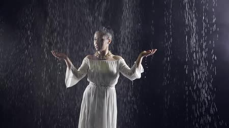 bohyně : woman in the image of an arabian princess is standing under night rain in darkness, catching drops