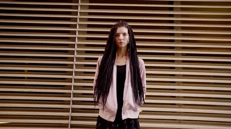 rendkívüli : emotionless teenager with dreadlocks is standing on background of construction from horizontal beams