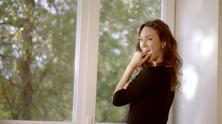 nibble : playful brown-haired woman is standing near big window, looking at a camera and flirting