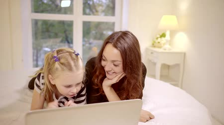 veselí : young woman is having fun time with her junior sister, watching cartoons on laptop in cosy bedroom