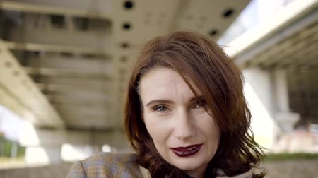 ninhada : close-up portrait of adult woman with short red hair and vivid make-up in sunny day under bridge Stock Footage