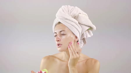 hydratují : woman is applying facial moisturising cream after shower, hair are wrapped in a towel