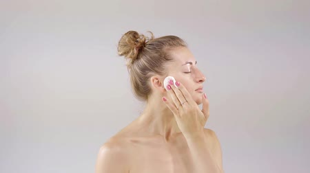 insan vücudu : pretty woman is cleaning her face and neck by cotton pad, turning head and looking to a camera Stok Video