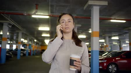 affluent : woman is standing in underground parking, holding coffee in a paper cup and talking by phone