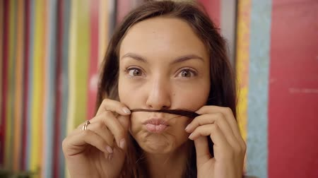 fool : cheerful pretty girl is making herself mustaches from her strand of hair