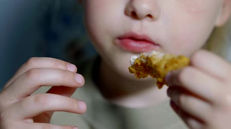 ekmekli : close-up, baby girl eating fast food. chicken strips in batter Stok Video