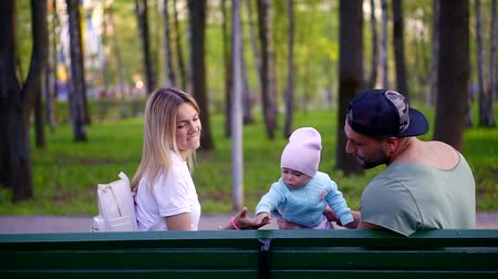 acalmar : young family sitting on bench in park, husband and his wife playing with little child Stock Footage