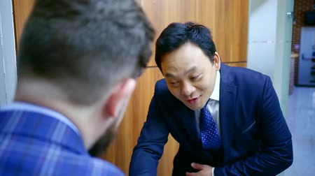 povinnost : Asian business partner bows to a European man during a meeting before the talks