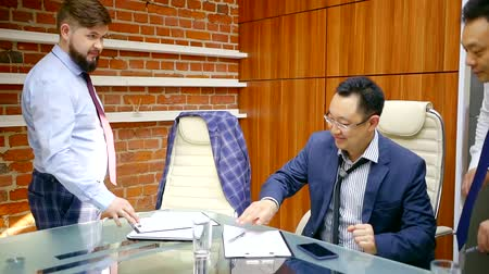 povinnost : a young man brings a contract for signing for Asian clients who sit in the office