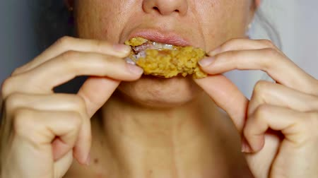caloric : close up. middle-aged woman eating fast food chicken wing spicy battered