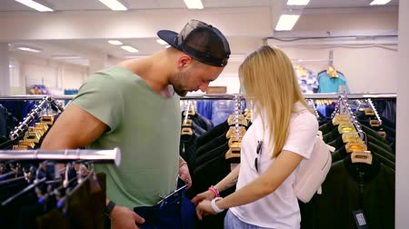 grande grupo de objetos : Lovely young couple at the mall choosing jeans for man. Vídeos