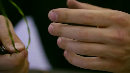argon : close up shot of the mans hands, who strips the wire in order to cut it into two halves