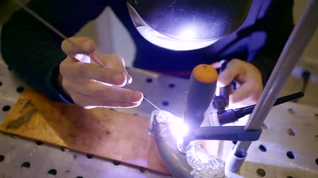 argon : A portrait of a man wearing a mask on his head, a welder works in the workshop to seal the aluminum part Stock Footage