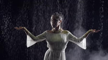 homeopathic : young Arab girl in a white national dress of the night wet in the rain Stock Footage