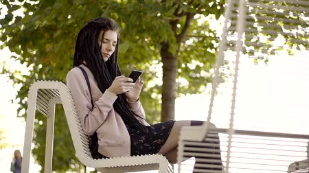 pankáč : Woman using apps on your smartphone the text on your mobile phone. Young woman using smartphone in city Park, Steadicam shot