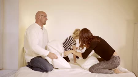 minder : happy cheerful family playing with pillows on the bed in the bedroom
