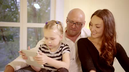 middle : happy young family at home in the bedroom on the bed. daughter plays on a tablet computer and does not allow the mother to interfere in the process. dad with glasses is watching what is happening