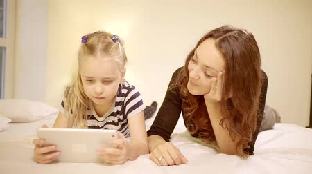 puericultura : Beautiful Mother and Her Little Daughter Have Good Time Reading Childrens Books on a Tablet Computer. Stock Footage