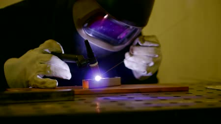 argon : Close up shot of welder using argon for welding two parts in a workshop.